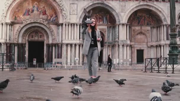 Happy beautiful female tourist with smartphone and pigeons on hand at San Marco square in Venice, Italy slow motion.