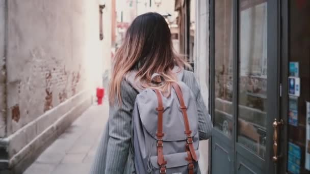 Camera follows stylish female tourist with backpack and long hair walking along old summer street in Venice slow motion.