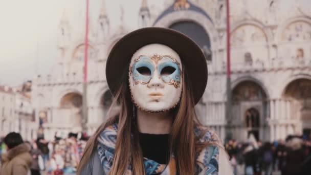 Porträt einer Frau mit langen Haaren mit Hut und Karnevalsmaske, die an der Kathedrale San Marco in Venedig in Zeitlupe steht.
