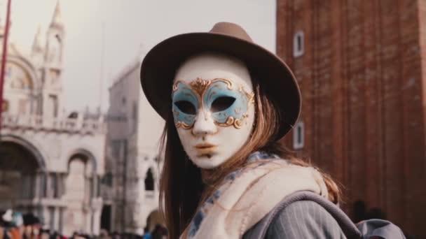 anonyme Frau mit langen Haaren blickt in die Kamera und trägt Karnevalsmaske auf dem venezianischen San Marco City Square in Zeitlupe.