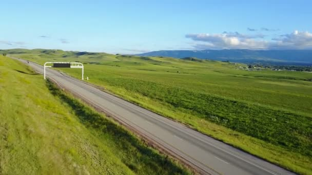 Beautiful aerial background shot of highway going through peaceful grassland hills and distant mountains with clear sky.