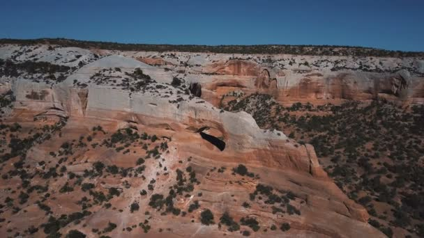 Drone flying high around incredible Arches rock formation with tourists inside exploring amazing national park mountains