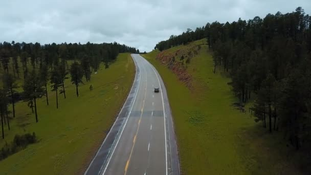 Drone follows silver car moving along concrete highway between wild green forest rocky hills panorama covered with trees