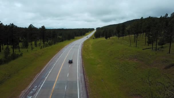 Static drone shot of traffic cars moving along concrete highway between wild green forest rocky hills on a cloudy day.
