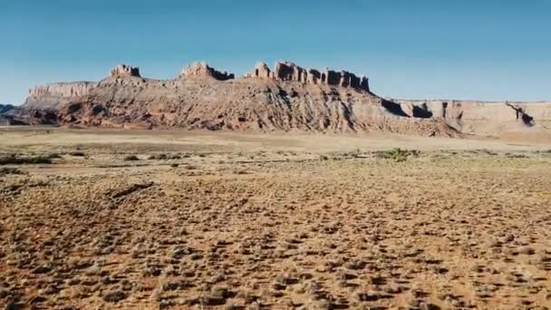 Létající DRONY přes suché pískovec desert směrem k úžasné plochý vrchol hory a modré nebe nad hlavou v americké národní park.