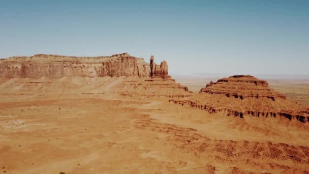 Drone flying over sunny dry desert towards big rocky mountains and clear blue sky in Monument Valley national park.
