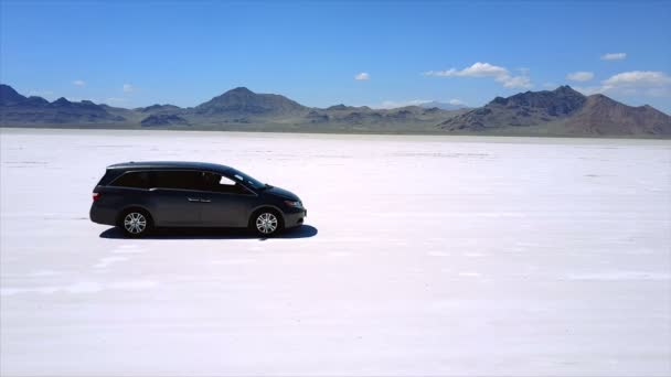Aerial shot of silver minivan car standing in the middle of Bonneville salt lake desert flats, drone making sharp moves.