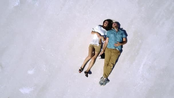 Amazing top view drone shot of peaceful happy young man and woman lying together in the middle of salt lake desert.