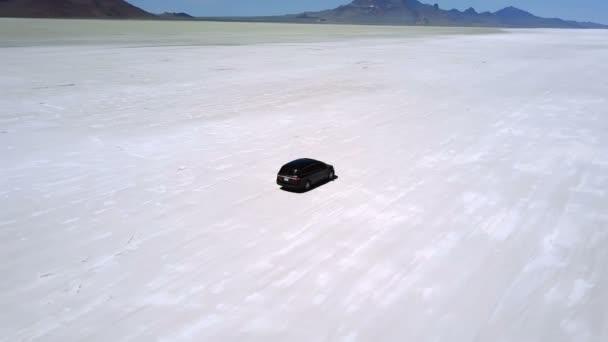 Atmospheric aerial shot of silver minivan car standing in the middle of incredible Bonneville salt lake desert flats.
