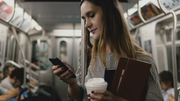 Happy successful confident businesswoman passenger on the subway train using smartphone e-commerce shopping app smiling.
