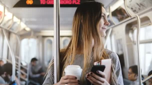 Happy relaxed beautiful female freelancer riding on the metro train looking at smartphone using shopping app smiling.