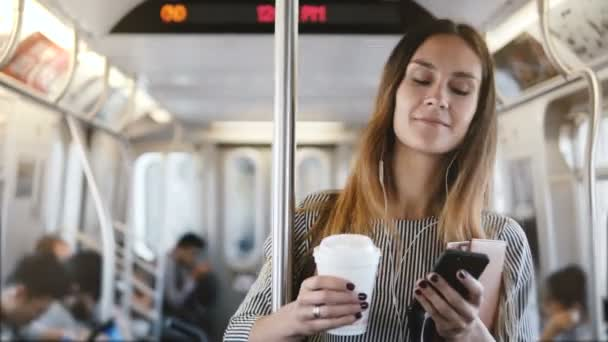Happy relaxed beautiful millennial girl stands in subway train looking at smartphone using e-commerce mobile app smiling