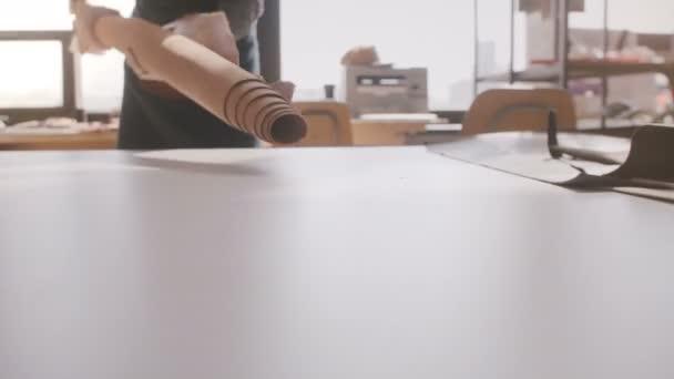 Detailní pohled profesionální řemeslník podnikatel šíří velký kus kůže na světlo výrobní dílna tabulka
