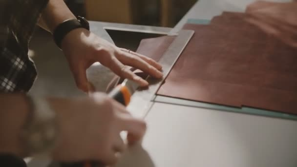 Krásný detail záběr ženské ruce řezání velké kožené kus na stole světlo workshop s nožem a křivka pravítka