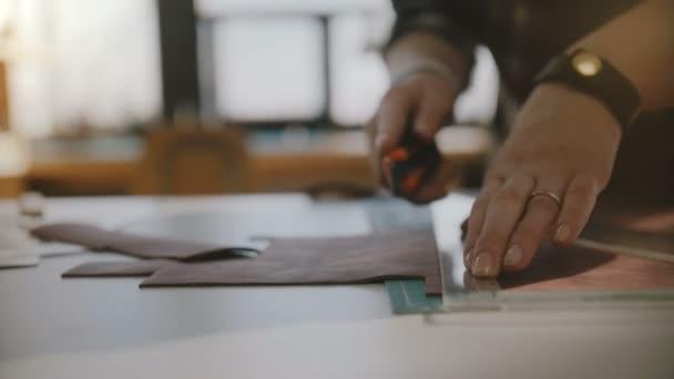 Schöne Nahaufnahme der Fachmann weibliche Hände große Leder Stück auf Tisch mit Messer und Dreieck Lineal schneiden