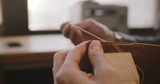 Close-up shot mužské ruce šití koženou tašku na Sedlář s jehlami v lehké moderní výrobní dílna
