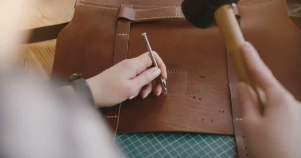Pohled shora Close-up shot z profesionálních ženských rukou dělání otvorů v velkou koženou tašku s kladivem a ruku punč