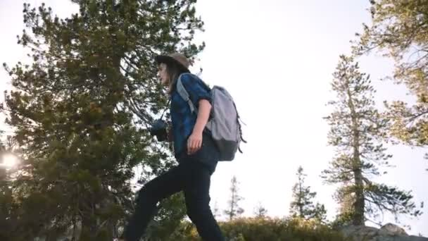 Young beautiful tourist girl with backpack and camera hiking alone on big rocks at Yosemite national park slow motion.