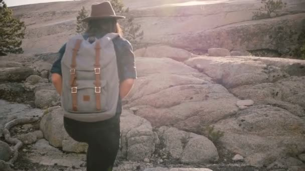 Happy beautiful tourist girl with backpack hiking on big rocks exploring sunny Yosemite national park forest slow motion