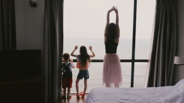 Young happy mother with two little kids together jumping and having fun at large window with epic sea view slow motion.