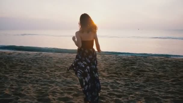 Camera follows happy excited female traveler in beautiful dress running to coming ocean wave to watch sunset on beach.