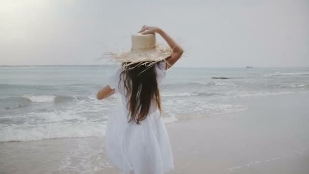 Happy beautiful 5-7 year old girl with flying hair and big straw hat running along cinematic tropical exotic ocean beach