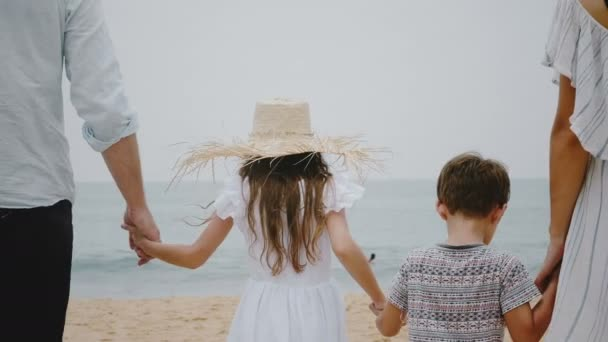 Back view close-up happy Caucasian family of four walking to ocean waves along tropical beach together holding hands.