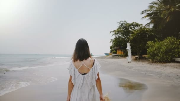 Slow motion camera follows young beautiful happy tourist woman walking along idyllic tropical ocean beach with straw hat