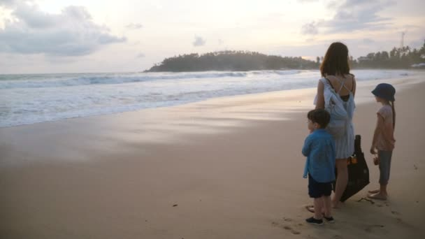 Back view happy young mother together with two kids watching incredible atmospheric sunset at exotic tropical sea beach.