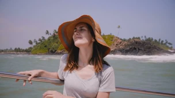 Happy beautiful young female tourist enjoying amazing exotic sea cruise boat trip on vacation on a sunny windy day.