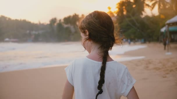 Csodálatos hát Nézd lövés boldog békés kis 6-8 éves női gyermek állt a napsütéses trópusi sunset strandtól.