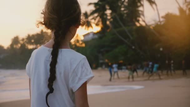 Amazing back view shot of little happy girl on tropical exotic sunset sea beach watching local people play volleyball.