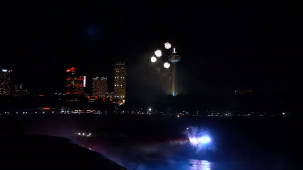 NIAGARA FALLS AUG 17 2018 Series of firework explosions blow up over nighttime waterfall and city buildings slow motion.