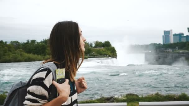 Happy tourist woman with backpack, smartphone and map walking along and watching epic Niagara waterfall slow motion.