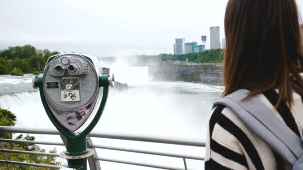 Happy tourist woman with backpack walks up to coin operated telescope at Niagara waterfall observation deck slow motion.