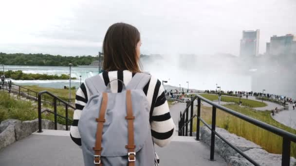 Camera follows tourist woman with backpack walking towards crowded observation deck at famous Niagara Falls slow motion.