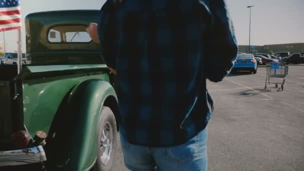 Back view of young beautiful American woman walking by cool green vintage pickup truck with USA flags slow motion.