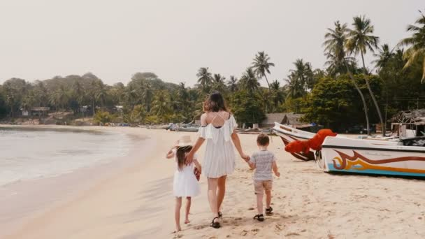 Camera follows happy young mother with two little children walking along exotic beach on tropical vacation slow motion.