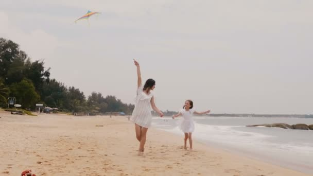 Happy little girl flying a kite, running around young mother on exotic beach during tropical summer vacation slow motion