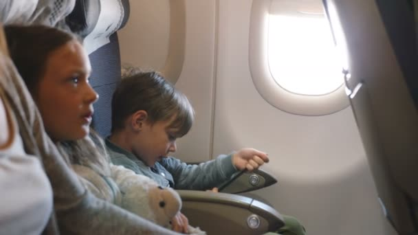 Side view of little bored boy and girl entertaining themselves during airplane flight going to vacation with family.