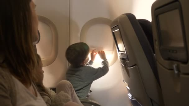 Happy excited little boy opening airplane window cover during flight going to vacation trip smiling together with family