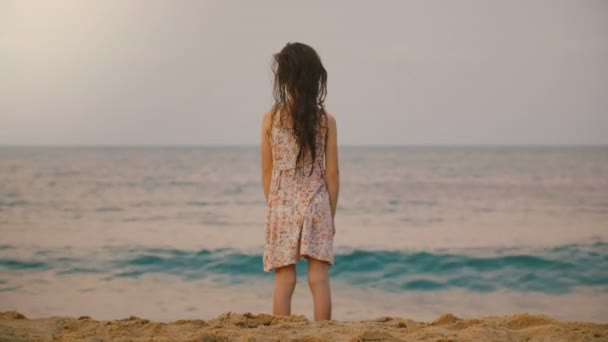 Beautiful back view shot of little 6-8 years old girl watching big waves on tropical exotic ocean beach in Sri Lanka.