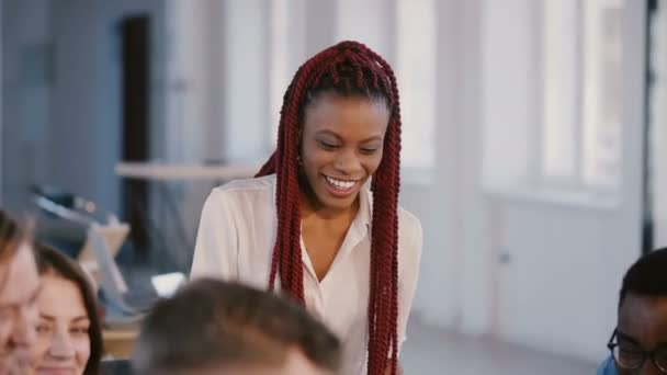 Young casual positive African American female company boss talking to partners, smiling at mixed race team meeting.