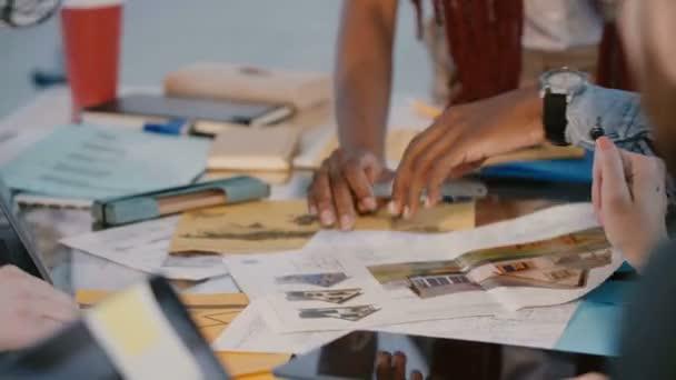 Blízcí partneři společnosti pro rozvoj multietnického rozvoje spolupracují, pracují společně nad kancelářskou tabulkou plnou papírových dokumentů.