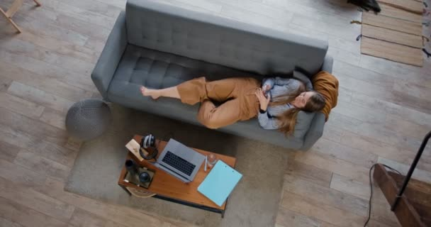 Top view young beautiful relaxed blonde woman lying down on cozy sofa using smart phone social network app at home.