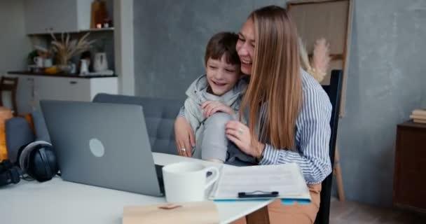 Rodinná zábava doma. Mladý šťastný kavkazský matka a 6-8 letý syn mají čas spolu sledovat kreslené filmy na notebooku.