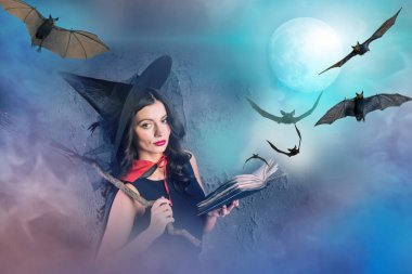 halloween witch holding book with bats and moon on background