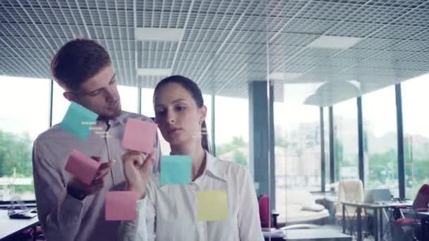 mladý podnikatel psaní na skleněnou tabuli v kanceláři