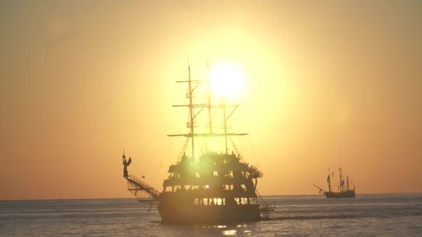 stará pirátská loď plující při západu slunce