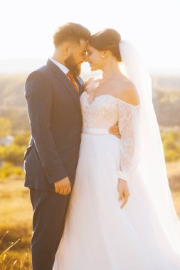 Couple embracing face to face dressed in wedding clothes is standing in sunlight.